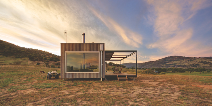 Ramshackle prefabricated cabin at the foot of the Snowy Mountains in Tintaldra, Australia. SITUATED ON A VAST PROPERTY ON THE SOUTHERN BANKS OF THE MURRAY RIVER IN TINTALDRA, APPROXIMATELY 100KM EAST OF ALBURY, THIS UNIQUE HOME SERVES AS AN AUSTRALIAN BASE FOR A CLIENT LIVING OVERSEAS AND OFFERS A SECLUDED YET INTIMATE EXISTENCE FROM WHICH THE SURROUNDING ENVIRONMENT CAN BE OBSERVED AND REVERED. As a small boutique project, the design brief required a single-module cabin that was completely offgrid and easily maintained during long periods of unoccupancy throughout the year. A cladding system was subsequently developed to create a salvaged, shed-like exterior, consisting of a base layer of new zincalume and a top layer of recycled zincalume which was applied for effect. When viewed from the road, the cabin recedes into the landscape by looking like any number of sheds in the area and appears as a small silhouette against the main range of the snowy mountains on the horizon. As a stark contrast, the interior floorplan is crisp white with clean lines and contemporary fittings and fixtures, although the environment continues to be referenced in punctuations of timber flooring, decking, and a wood fire heater that invites the outdoors in. Minimalistic in layout, the cabin provides all the amenities needed for living including a master bedroom, bathroom and modest open plan kitchen/living/dining area, while solar panels, a septic tank and a rainwater tank ensures year-round services and minimal environmental impact.
