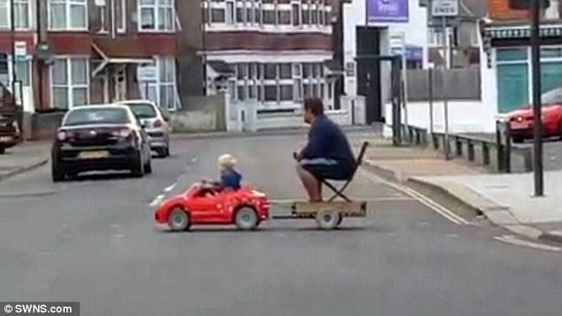 Dieťa ťahá za svojím mini autíčkom otca sediaceho na stoličke. Aké boli reakcie ľudí?