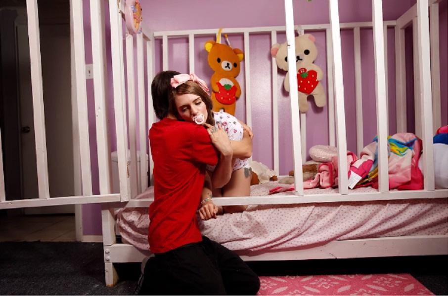Cmúľa si svoj prst, spí v postieľke, nosí plienky a oblieka si dupačky. Má však 21 rokov!
